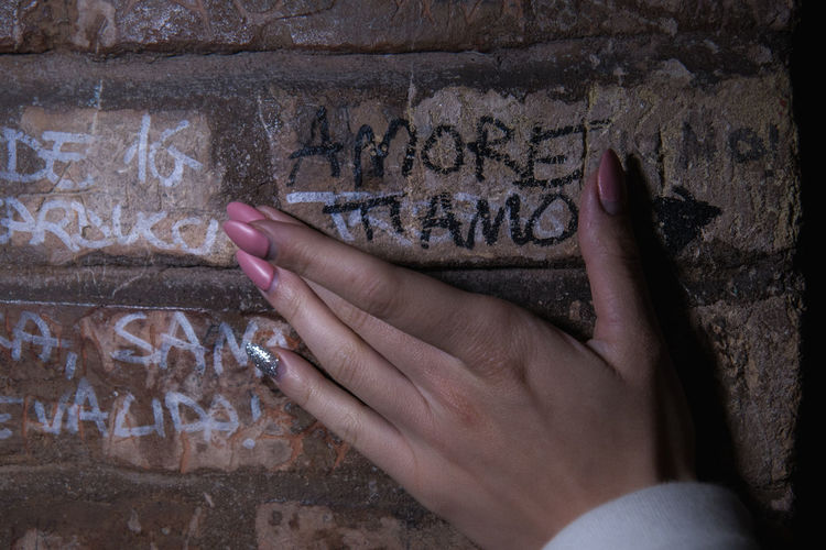 Cropped hand of woman touching brick wall with text
