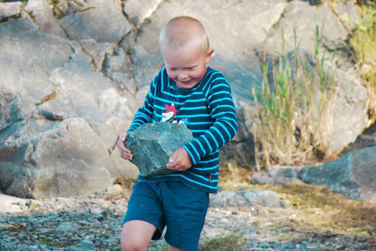Full length of a boy holding rock