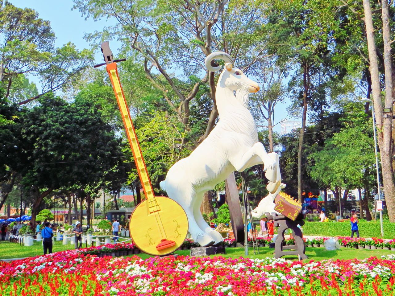 tree, horse, animal representation, day, outdoors, park - man made space, sculpture, statue, sky, multi colored, carousel, no people, nature, animal themes