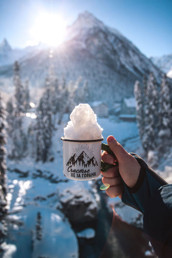 Mug with snow in hand on a background of mountains