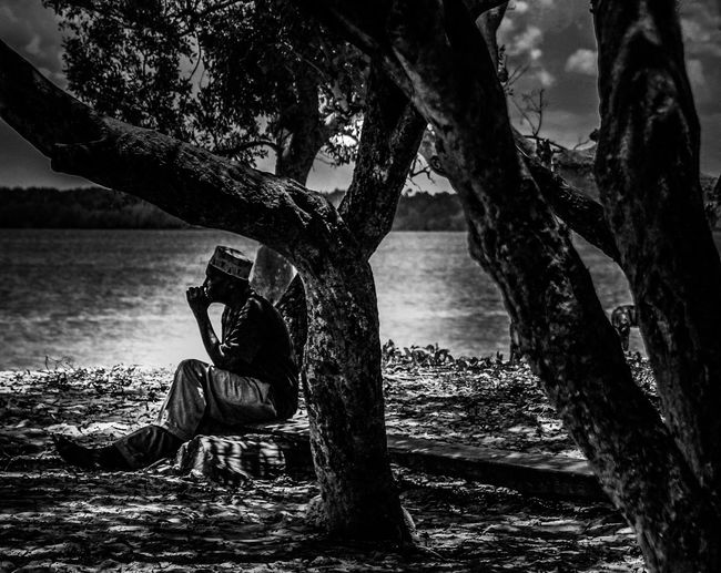 Break In The Shade Break Under Trees Intermission Man At The Sea Man At The Water Resting Place Sitting Man At The Water Sitting Under Trees Tranquil Scene On The Water Black And White Black And White Friday Blackandwhite Full Length Human And Nature Nature Relaxation Rest Resting Sitting Sitting Man Sitting Under Trees Tranquil Scene Tranquil Scene Nature Tranquil Scene Outdoors Tree Trunk Summer Exploratorium Visual Creativity Focus On The Story
