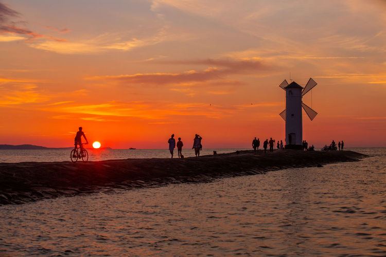 Baltic Sea Stawa Mlyny Beach Beauty In Nature Cloud - Sky Group Of People Holiday Horizon Horizon Over Water Human Arm Land Leisure Activity Lifestyles Nature Orange Color Outdoors Real People Scenics - Nature Sea Silhouette Sky Sunset Water