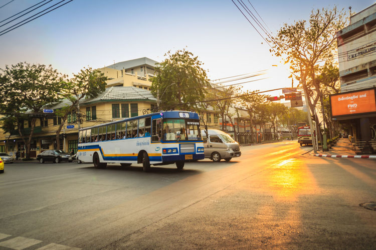 Bangkok, Thailand - March 2, 2017: Local bus and cars in traffic passes through a busy junction during sunset in Bangkok, Thailand. Junction Sunset And Clouds  Traffic Traffic Jam Traffic Signs Architecture Building Exterior Built Structure Car City City Street Day Junctionsquare Land Vehicle Local Bus Mode Of Transportation Motion Motor Vehicle Nature Outdoors Plant Residential District Road Sky Street Sunlight Sunset Traffic Arrow Sign Traffic Light  Traffic Lights Traffic Sign Traffic Signal Trafficjam Transportation Tree