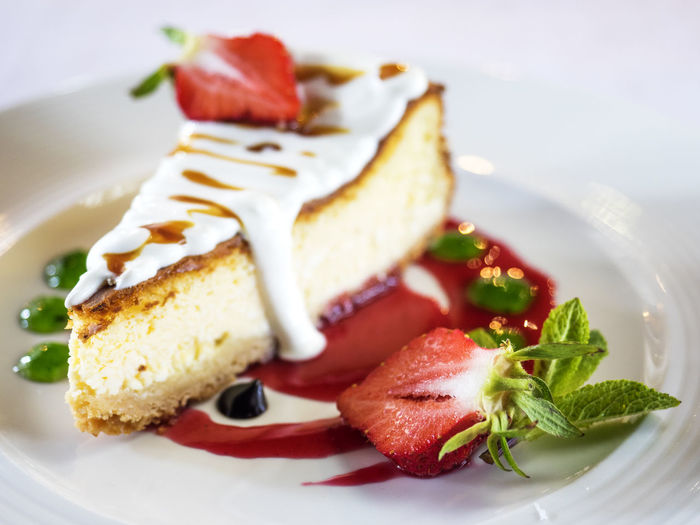 Close-up of cheesecake with cream and strawberries served on table