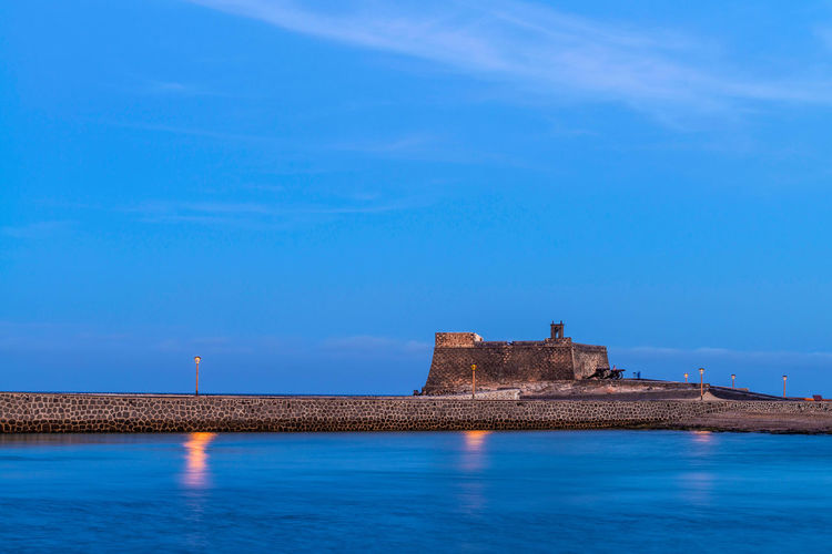 River In Front Of Illuminated Castillo De San Jose Against Sky During Dusk