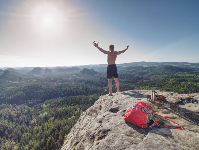 Shirtless sportsman take off backpack and rope on top of mountain and raised arms to greeting nature