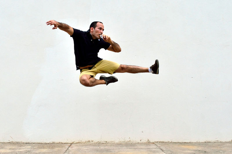 Young man doing a flying kick while eating