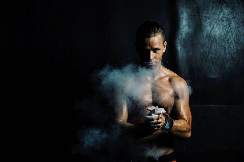 Portrait of muscular man dusting powder in gym