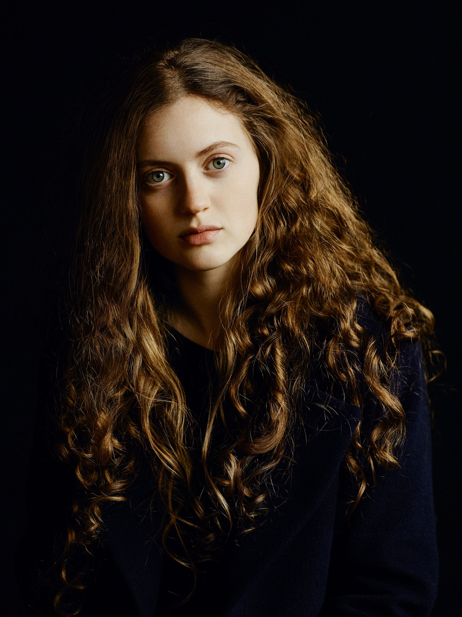 studio shot, young adult, black background, young women, looking at camera, long hair, front view, one person, portrait, real people, beautiful woman, curly hair, lifestyles, indoors, close-up