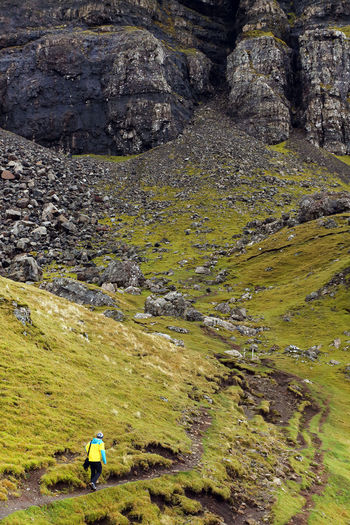 Rear view of man walking on storr at isle of skye against mountain