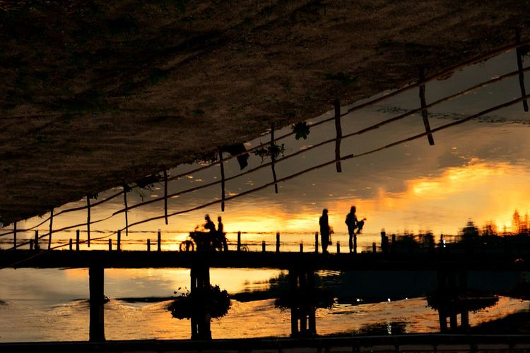 Silhouette people by railing against sky during sunset