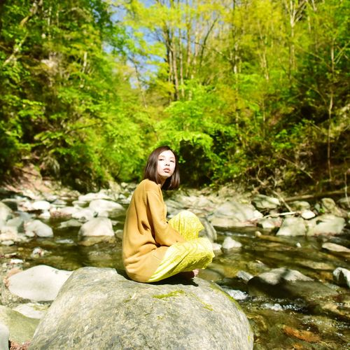 Woman sitting on rock against trees in forest