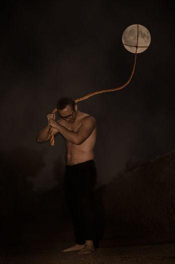 Optical illusion of shirtless man pulling moon at night
