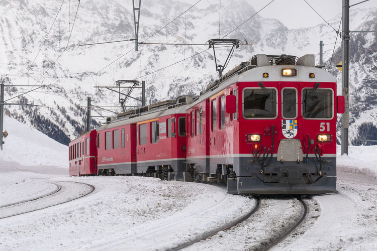 Bernina Express Alp Grüm Bernina Cable Car Cold Temperature Day Ferrovia Del Bernina Land Vehicle Mode Of Transportation Nature No People Outdoors Public Transportation Rail Transportation Railroad Track Red Retica Snow Snowcapped Mountain Snowing Track Train Train - Vehicle Transportation Travel Tree Winter