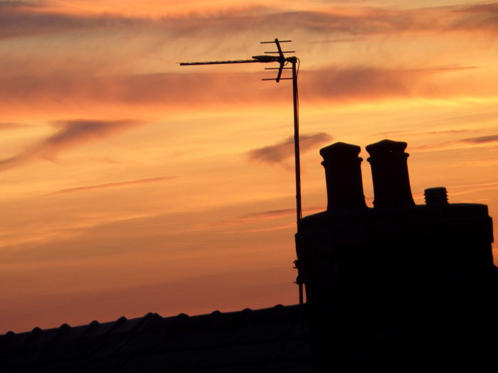Low angle view of silhouette television antenna and building at sunset