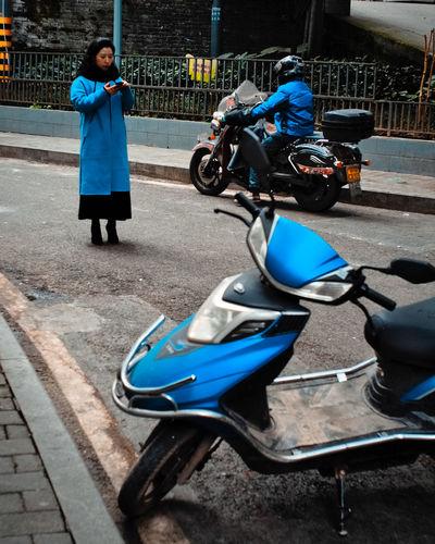 Man riding motor scooter on street