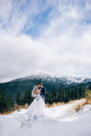 Woman playing with snow on mountain against sky
