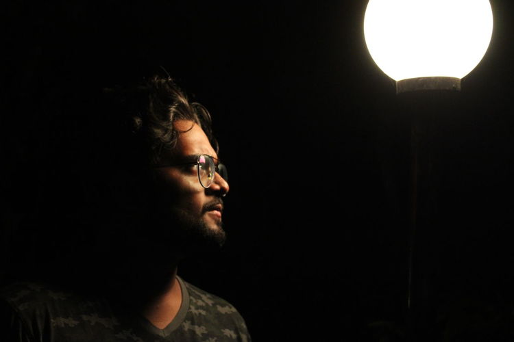 Man looking at illuminated pendant light against black background