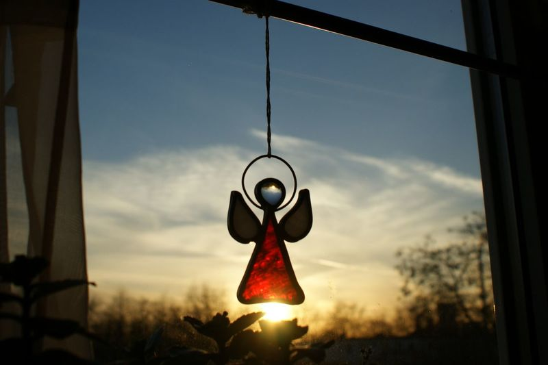 Low Angle View Of Angel Figurine Hanging On Window Against Sky During Sunset
