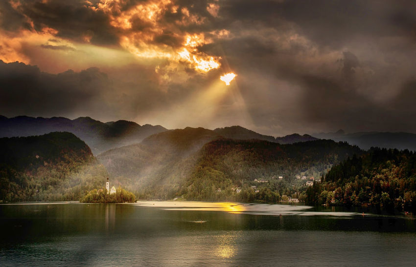 Evening light on Lake Bled Island Bled Awe Beauty In Nature Cloud - Sky Day Dramatic Sky Idyllic Lake Landscape Mountain Mountain Range Nature No People Outdoors Reflection Scenics Sky Storm Cloud Sunset Tranquil Scene Tranquility Tree Water Waterfront Weather