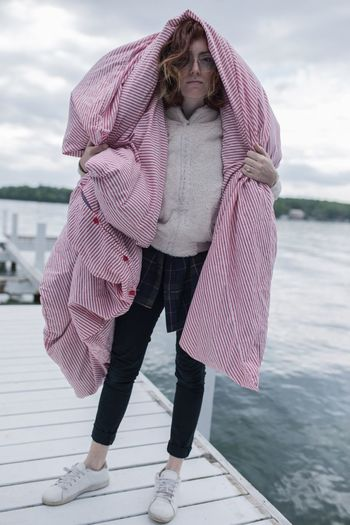 Full length of beautiful woman standing on jetty against lake