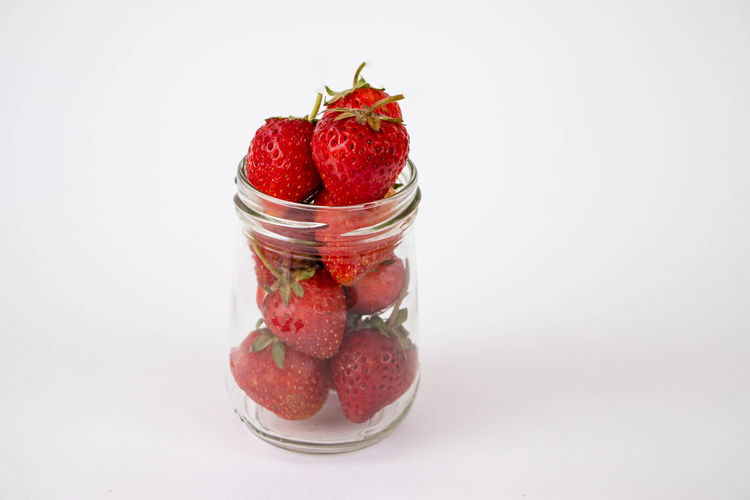 Close-up of strawberries in glass jar against white background