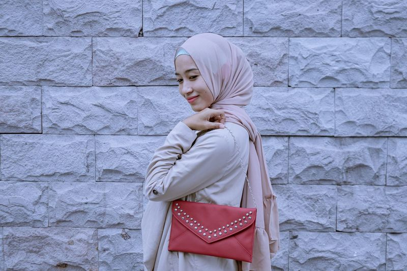 Side view of smiling woman with purse wearing hijab while standing by wall