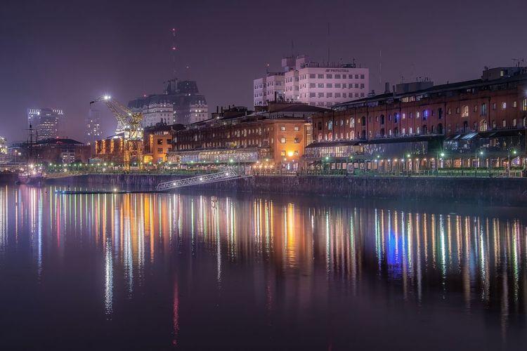 Illuminated buildings reflecting on river at night