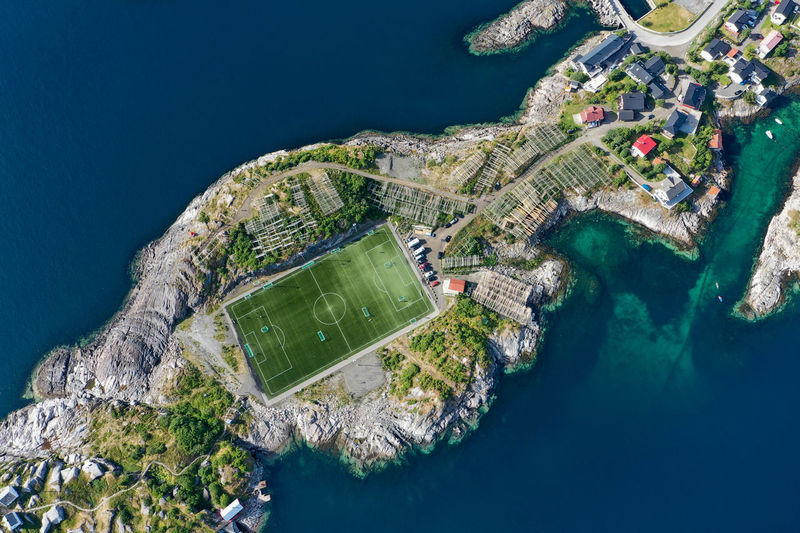 Drone view of a football field surrounded by ocean and cliffs in lofoten norway