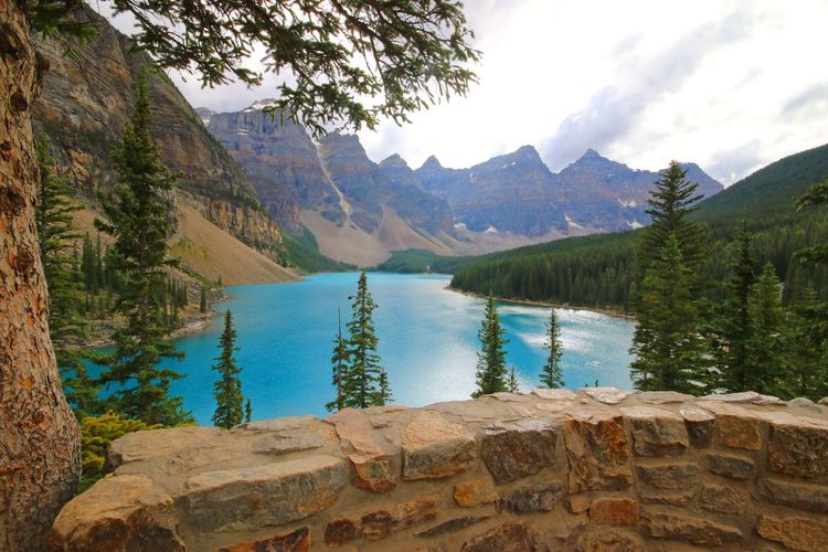 Scenic View Of Moraine Lake By Mountains Against Cloudy Sky