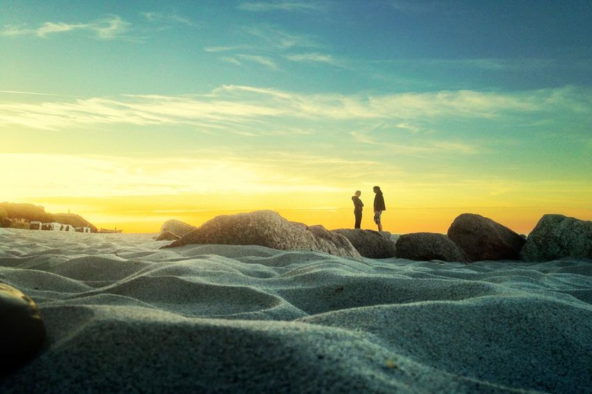 Man and women talking to each other at the beach in front of sundown Beach Cloud Discus Horizon Over Land Light Low Angle View Majestic Nature Non Urban Scene Non-urban Scene Outdoors Sand Sky Skyporn Stone Sundown Sundset Tranquil Scene Tranquility
