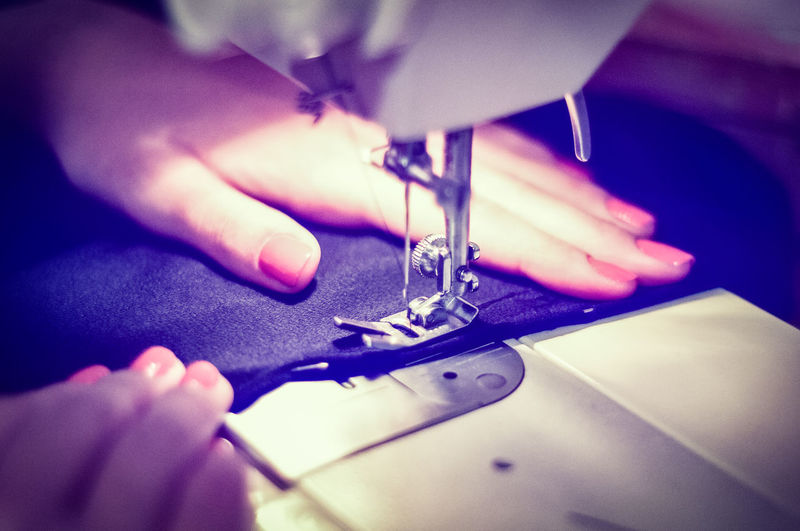 Cropped image of woman stitching fabric on sewing machine