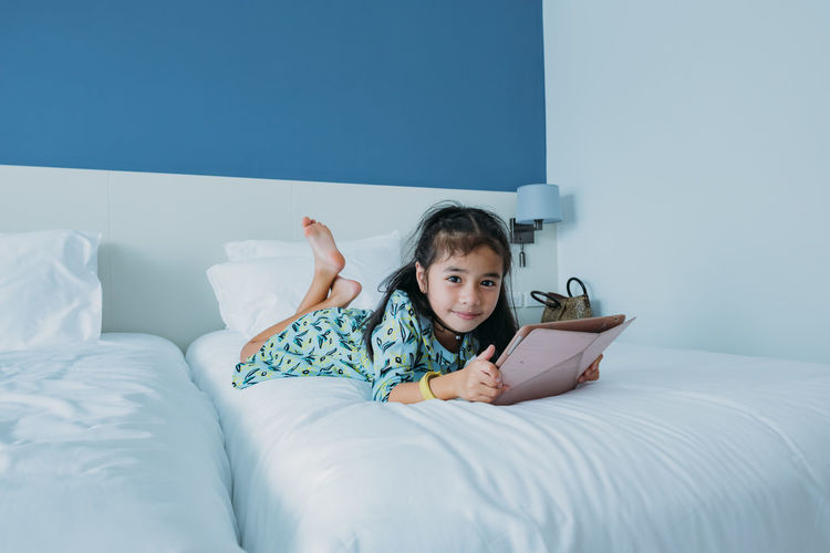 Portrait of boy lying on bed