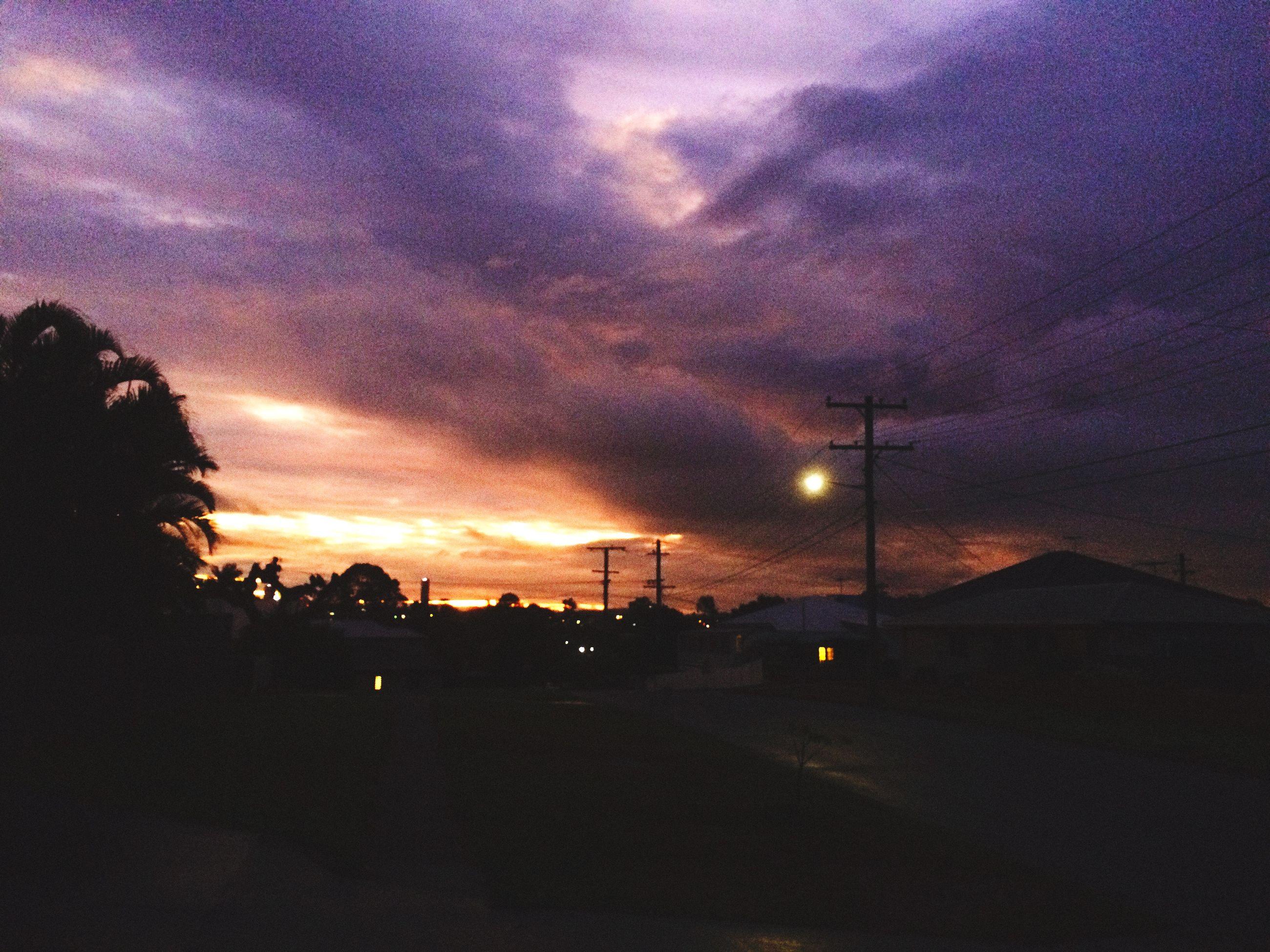 sky, cloud - sky, illuminated, night, silhouette, cloudy, sunset, storm cloud, dramatic sky, building exterior, road, street light, weather, street, dusk, transportation, overcast, car, built structure, city
