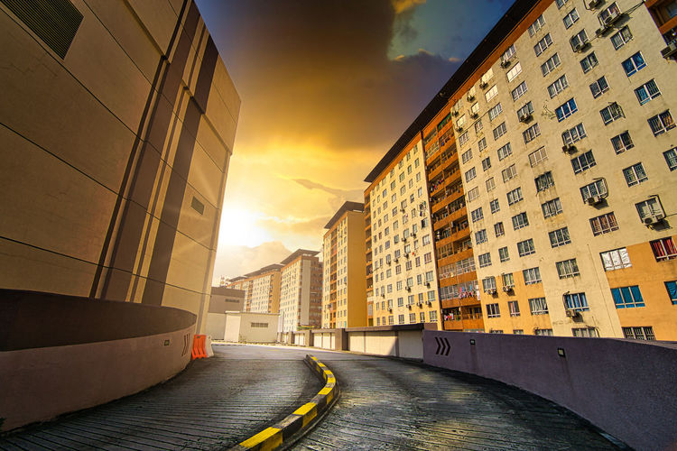 Empty road amidst buildings in city against sky
