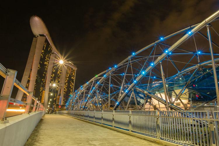 Modern bridge leading towards marina bay sands in city at night