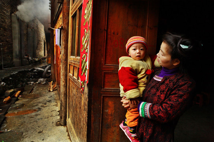Zengchong village, Guizhou, China - April 13, 2010: Chinese woman with child in her arms, stands on the village street, near a wooden house, April 13, 2010. Asian family from the rural areas, a mother holding two year old son in her arms, Zengchong village. Rural Family Rural Daughter Positive Emotion Warm Clothing Family Females Women Childhood Child Two People ASIA Chinese People Chinese Village Village Asian  Asiatic; People Chinese China Guizhou,