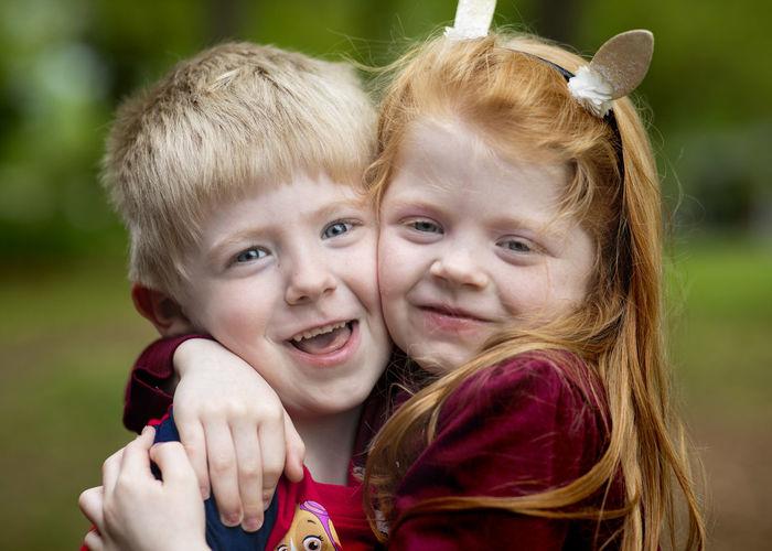 Portrait of happy siblings embracing at park