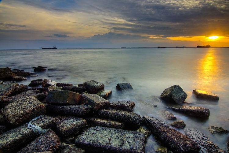Benua Patra Beach Sky Sea Water Sunset Cloud - Sky Scenics - Nature Beauty In Nature Rock Solid Tranquility Horizon Over Water Tranquil Scene Horizon Rock - Object Nature Land Beach No People Idyllic Outdoors Rocky Coastline