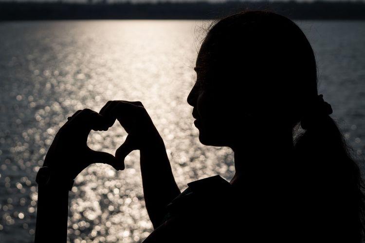 EyeEmNewHere Bokeh Sunset Heart Shape One Person Silhouette Water Background Handshape