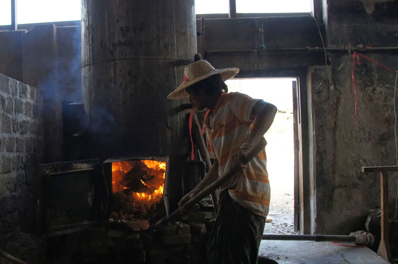 Factory worker in rice noodle factory ASIA Developing Country Fire Furnace Heat Shovel Worker At Work Young Nan