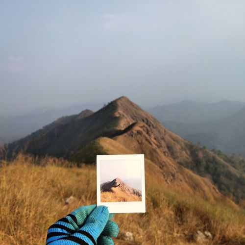 Cropped hand of man holding photograph against mountain and sky