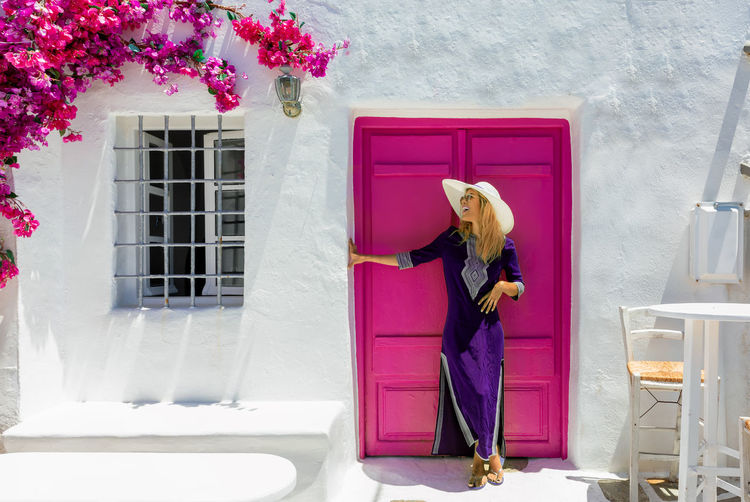 Blonde woman with purple dress stands in front of a classic cycladic setting with white house and colorful door, Greece, Paros One Person Architecture Pink Color Plant Building Exterior Flowering Plant Standing Women Real People Building Day Door Lifestyles Dress Blonde Model Greece Cyclades Paros Summer Island Travel Destinations Whitewashed Sightseeing Traveler