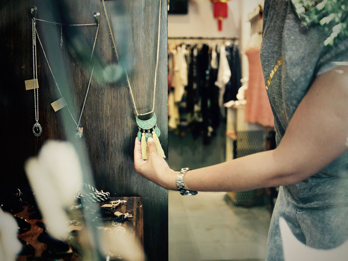 Midsection Of Woman Buying Necklace In Store
