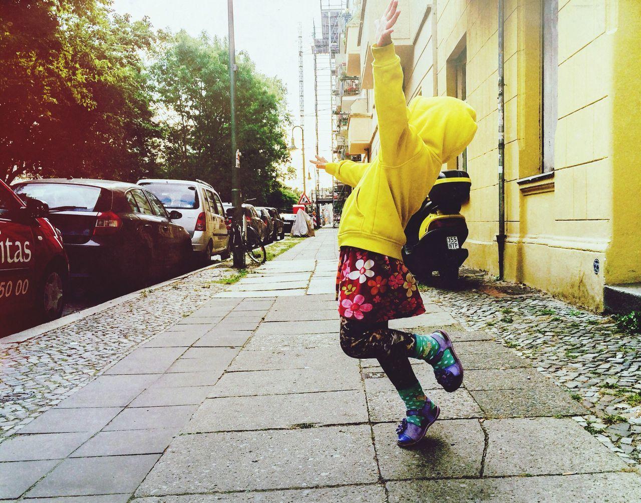 Full length of happy girl dancing on sidewalk