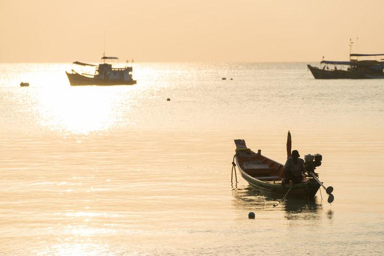 Fisherman in boat on sea against sky