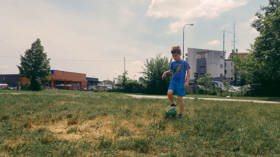 Boy playing with ball on field