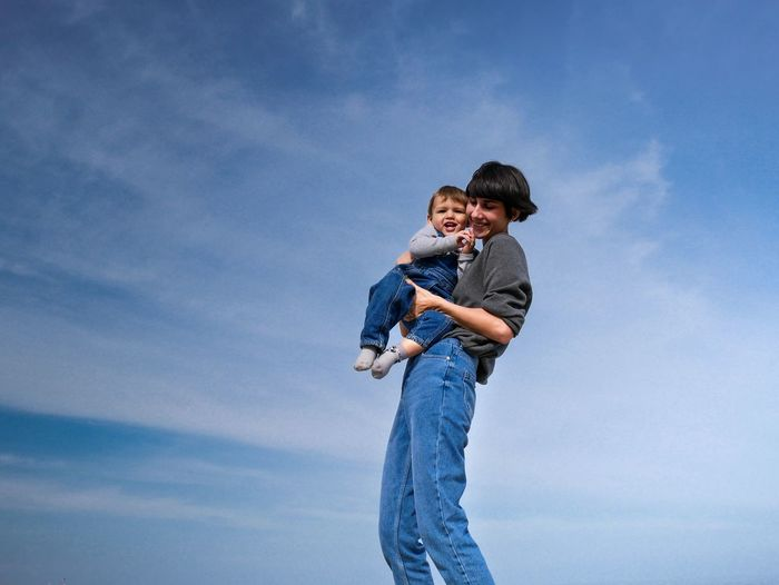 Smiling mother carrying son while standing against blue sky