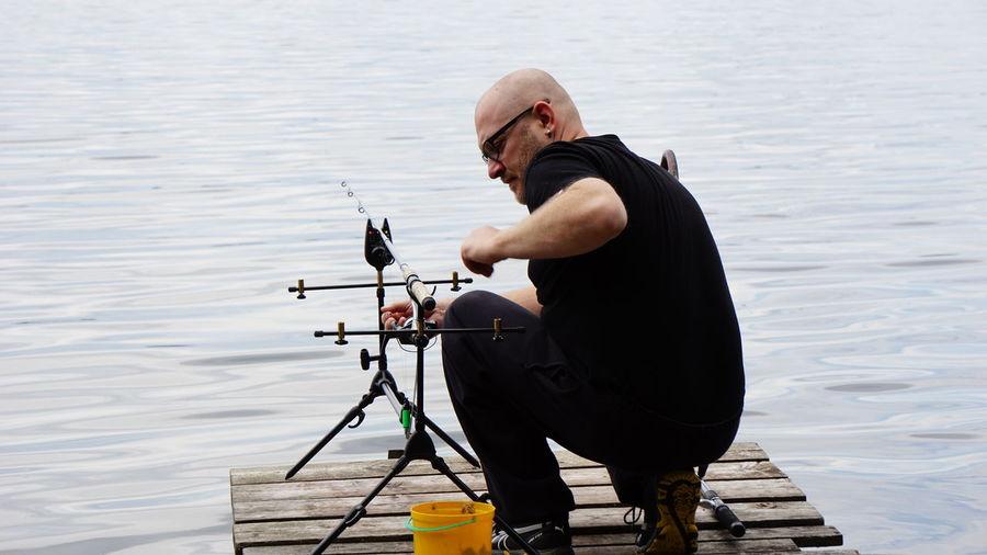 Bald Man Adjusting Fishing Rod On Pier Over Lake