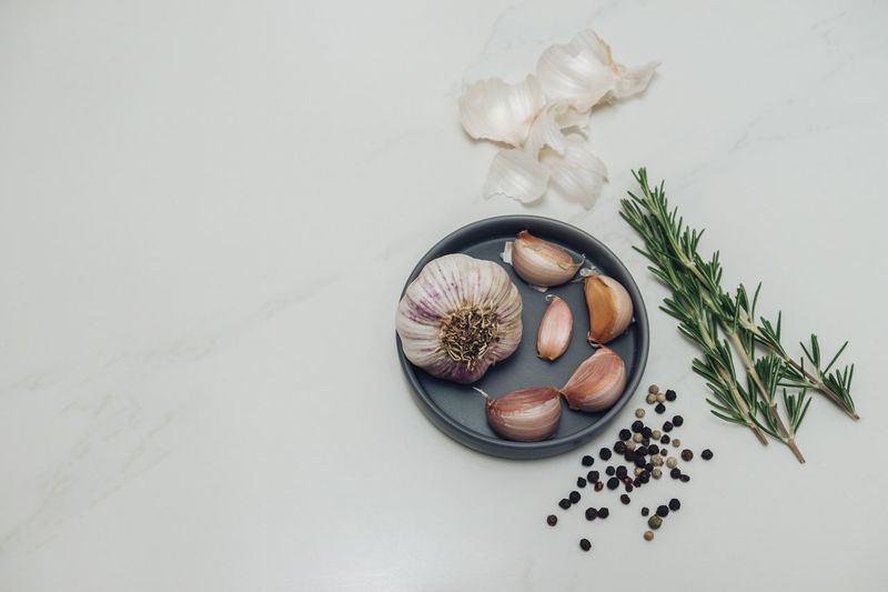 Garlic, Rosemary, Peppercorns and a Knife on white marble. Cooking Garlic Herb Herbs PEPPERCORN Peppercorns Rosemary Day Food Food And Drink Food Stories Freshness Garlic Garlic Bulb Garlic Clove High Angle View Indoors  Ingredient Lay Flat No People Pepper Spice Spices Table White Marble
